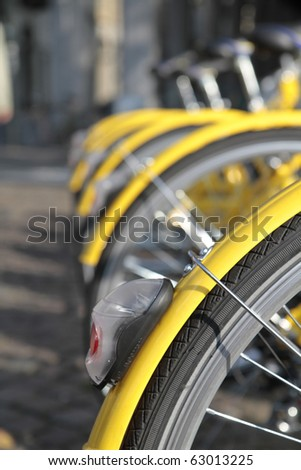 yellow bikes lined up in the city center in Turin Italy - stock photo