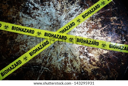 Yellow biohazard tape across and grunge metal background