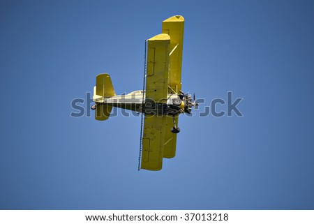 Yellow biplane, crop duster, flying against the blue sky. - stock photo
