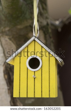 Yellow bird house hanging on a rope - stock photo
