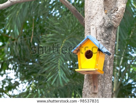 yellow birdhouse on a tree - stock photo