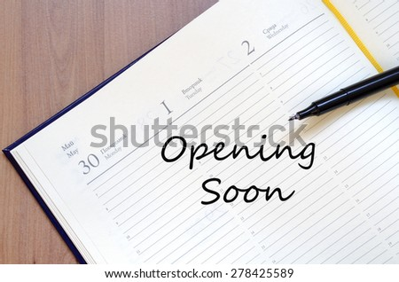 Yellow blank notepad on office wooden table Opening soon concept - stock photo