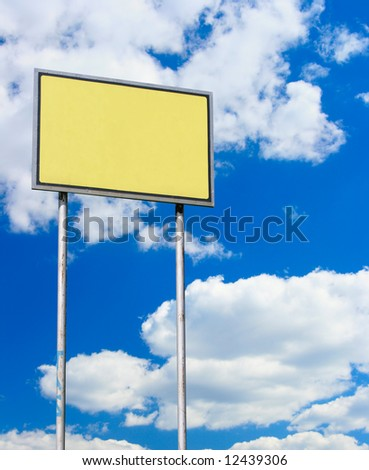 Yellow blank sign against blue sky with clouds - stock photo