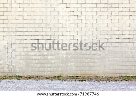 yellow block wall by gravel - stock photo