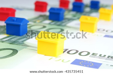yellow, blue and red small houses on the background of euro banknotes - stock photo