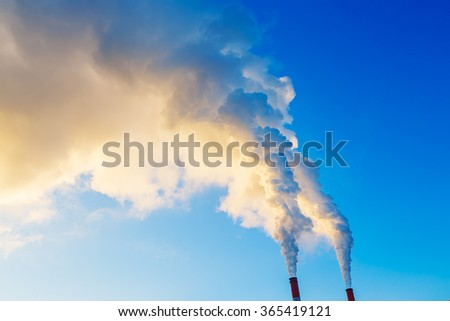 yellow blue smoke from two tubes of plant - stock photo