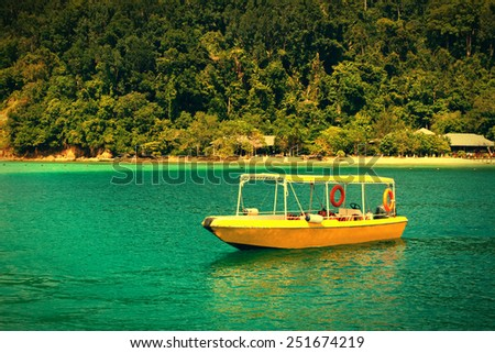 Yellow boat in a tropical bay. Vintage effect - stock photo
