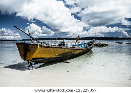 Yellow boat on a beach. ( HDR image ) - stock photo