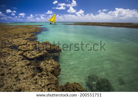 Yellow boat sailing at the sea in Porto de Galinhas, Brazil. - stock photo