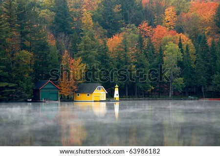 Yellow boathouse sits along the shore surrounded by the beauty of autumn/Yellow Boathouse/Autumn's colors highlight the beauty of the landscape. - stock photo