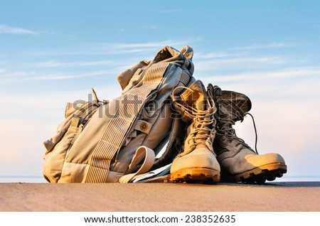 Yellow boots with a shoelaces and backpack on a sandy beach - stock photo