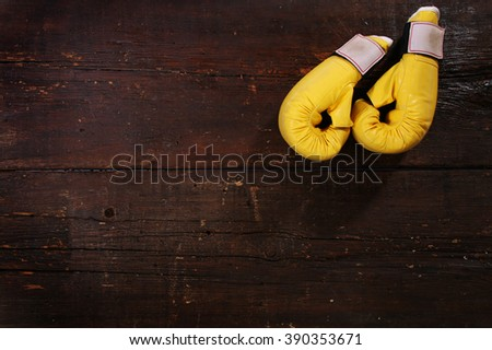 Yellow boxing gloves on a rusty wooden floor - stock photo