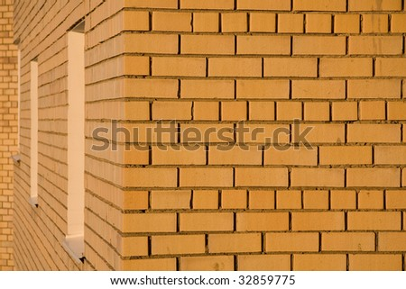 yellow brick wall in sunset light as it is - stock photo