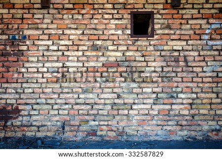 Yellow brick wall with one small window  - stock photo