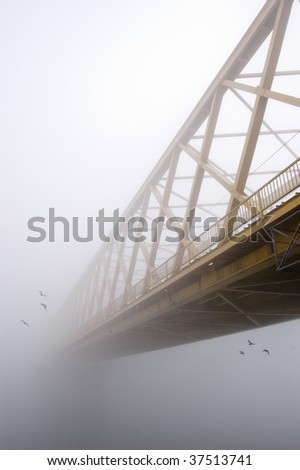 Yellow bridge disappears in the thick autumn fog. Two groups of three birds fly from the bridge in different directions. - stock photo