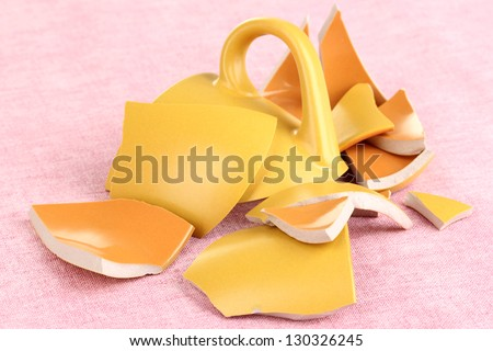 Yellow broken cup on table on pink background