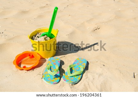 Yellow bucket and other toys at the beach - stock photo