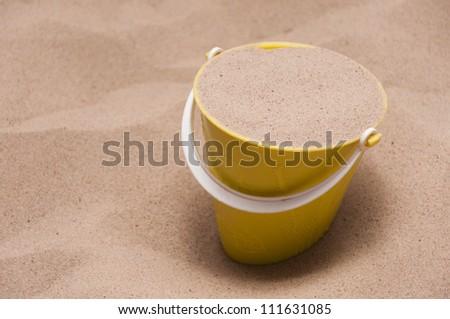 Yellow bucket and sand. - stock photo