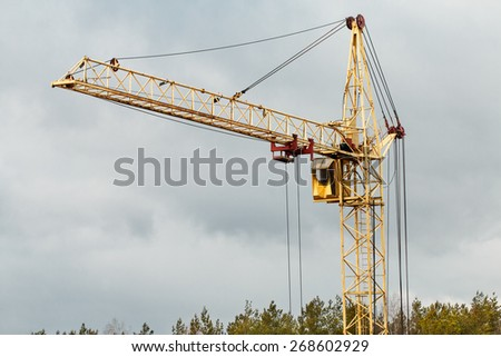 Yellow building tower crane. Construction concept - stock photo
