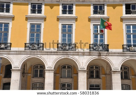 yellow building with portuguese flag surrounding Commerce Square in Lisbon, Portugal