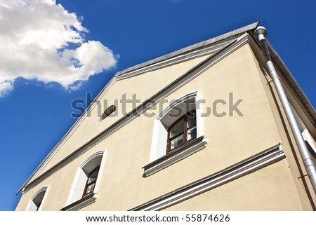 yellow building with windows over blue sky - stock photo