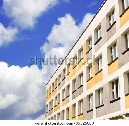 yellow building with windows over blue sky