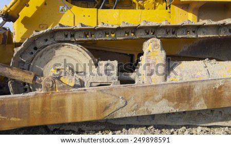 Yellow bulldozer in a field with blue sky. - stock photo