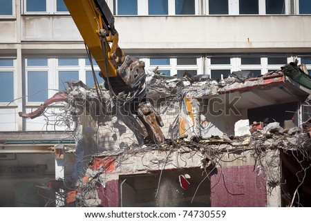yellow bulldozer is destroying an old building - stock photo