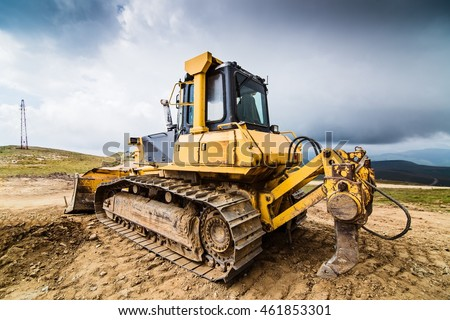 Yellow bulldozer on tracks at the mountain road construction