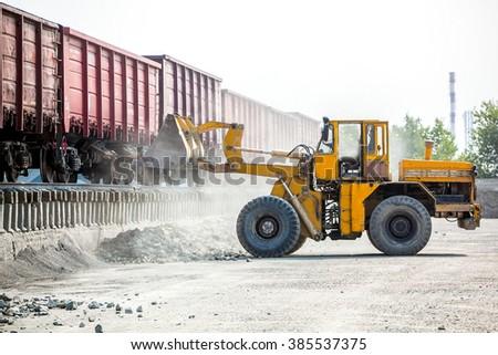 Yellow bulldozer working in quarry - stock photo