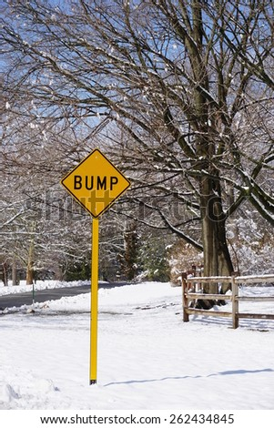Yellow bump road sign in a snowy landscape - stock photo