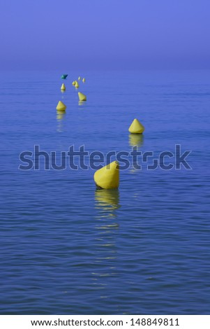 Yellow buoys with reflections on deep blue water, Majorca, Spain.