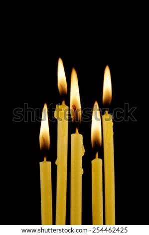 Yellow burning candles isolated on black  - stock photo