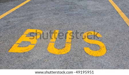Yellow bus sign on tarmac road - stock photo