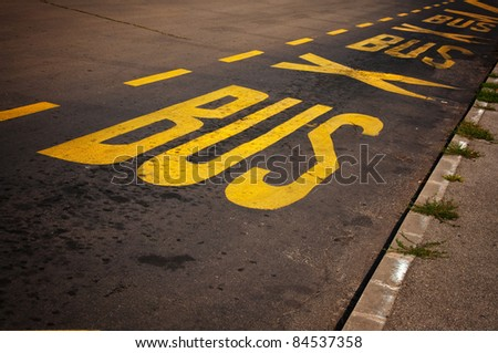Yellow Bus Stop sign painted on the asphalt