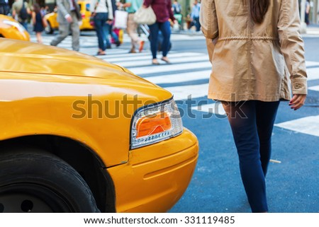 yellow cab waiting at a pedestrian crossing for crossing people in Manhattan, New York City - stock photo