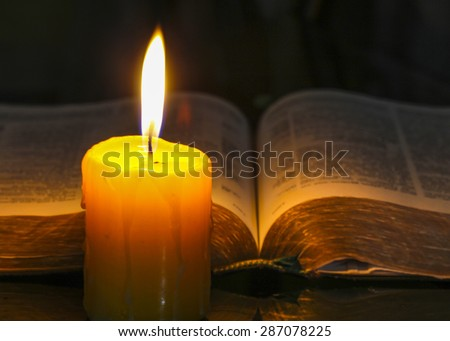 Yellow candle light with the holy bible in dark background - stock photo