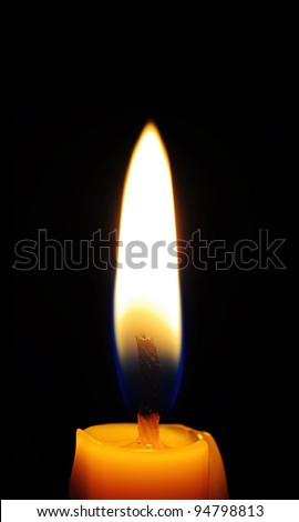 Yellow candle on the black - stock photo