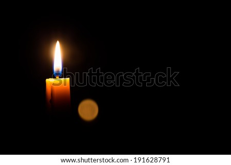 Yellow candle on the dark background and bokeh. - stock photo