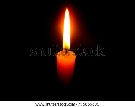 yellow candle with a orange and blue frame light with black shadow on background in the night of holy place