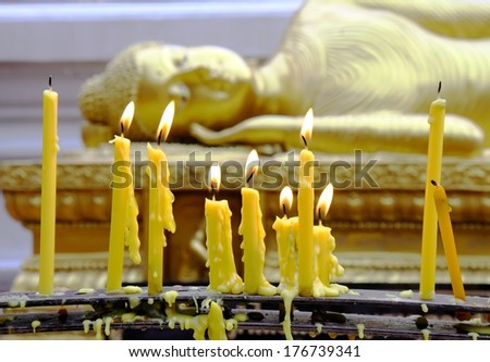 Yellow candles light at front of  Buddah - stock photo