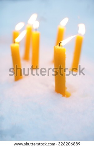 Yellow candles sitting in a base of snow - stock photo