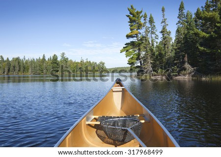 Yellow canoe with fishing net on a northern Minnesota lake with pine trees - stock photo