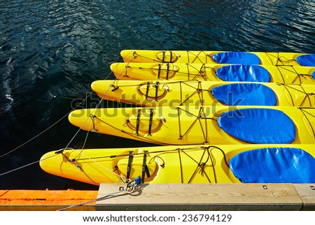 Yellow canoes, kayaks , 5 pieces, are on the water, attached to the shore, shrouded , tied a rope to the castle , around the water shines  - stock photo