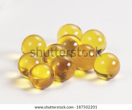 Yellow capsules near the box over light background