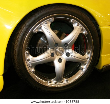 Yellow car with alloy wheel rim - stock photo