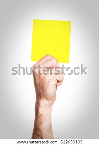 Yellow card: hand holding a yellow square - penalty