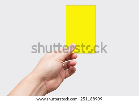 Yellow card in hands. Soccer referee is holdingYellow card, on white background. - stock photo