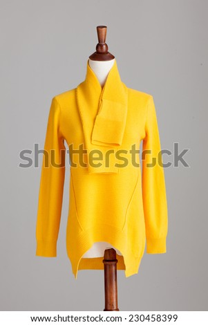 yellow cashmere sweater with wood model on grey isolated - stock photo