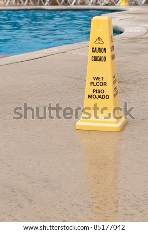 yellow caution sign regarding slippery surface next to a swimming pool (after a tropical storm)